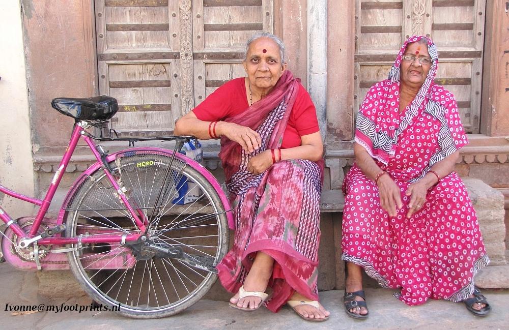 twee dames in het roze met hun roze fietsen in India